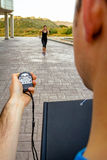 Trainer hand using chronometer to timing woman Stock Photo