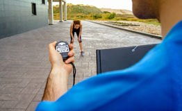 Trainer hand using chronometer to timing woman Royalty Free Stock Images