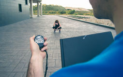Trainer hand using chronometer to timing woman Royalty Free Stock Photography