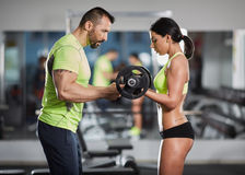 Trainer helping with biceps curl Royalty Free Stock Photography