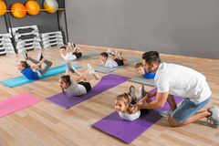 Trainer helping children to do physical exercise in school gym. Healthy lifestyle royalty free stock photography