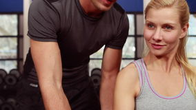 Trainer helping client lift weights. In high quality 4k format stock footage