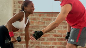 Trainer helping client lift weights. In slow motion stock footage