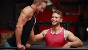 Trainer helping client to l hang in crossfit gym. In high quality 4k format stock video footage