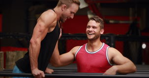 Trainer helping client to l hang in crossfit gym. In high quality 4k format stock footage