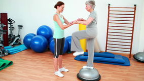 Trainer helping elderly client to use bosu ball stock video footage