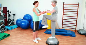 Trainer helping elderly client to use bosu ball stock video