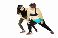Trainer helping fat woman doing workout Royalty Free Stock Photography