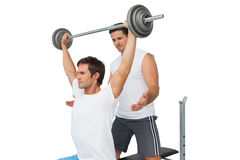 Trainer helping fit man to lift the barbell bench press Stock Photo