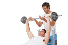 Trainer helping fit man to lift the barbell bench press Royalty Free Stock Images