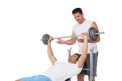 Trainer helping fit man to lift the barbell bench press Stock Photos