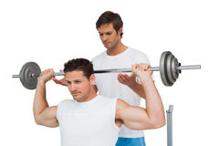 Trainer helping fit man to lift the barbell bench press Stock Image