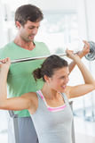 Trainer helping fit woman to lift barbell bench press Royalty Free Stock Photography