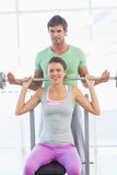Trainer helping fit woman to lift barbell bench press Stock Photos