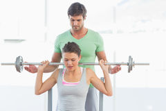 Trainer helping fit woman to lift barbell bench press. Male trainer helping young fit women to lift the barbell bench press in the gym Royalty Free Stock Photo
