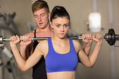 Trainer helping fit woman to lift the barbell in gym. Male trainer helping young fit women to lift the barbell in the gym Royalty Free Stock Photo