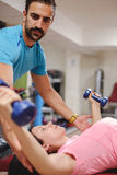 Trainer helping girl with chest flyes stock images