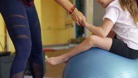 Trainer Helping Girl Exercising op Geschiktheidsbal stock video