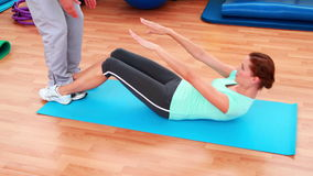 Trainer helping his client do a sit up. At the gym stock video footage