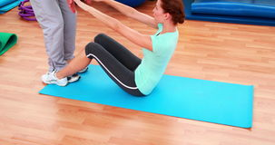 Trainer helping his client do a sit up. At the gym stock footage