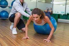 Trainer helping his client doing push up on exercise ball. At the gym Royalty Free Stock Photo