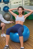 Trainer helping his client doing sit up on exercise ball. At the gym Royalty Free Stock Photo