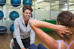 Trainer helping his client doing sit ups Royalty Free Stock Photography