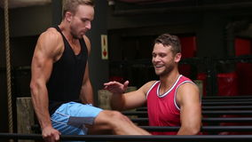 Trainer helping his client on parallel bars stock footage