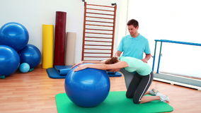 Trainer helping his client stretch her back with exercise ball stock footage