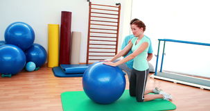Trainer helping his client stretch her back with exercise ball stock video
