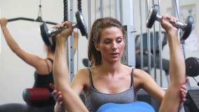 Trainer helping lying woman lifting weights. In gym stock video