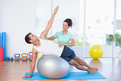 Trainer helping man with exercise ball. Trainer helping men with exercise ball in fitness studio Stock Photo