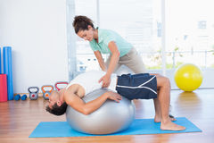 Trainer helping man with exercise ball. Trainer helping men with exercise ball in fitness studio Stock Photos