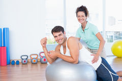Trainer helping man with exercise ball. Trainer helping men with exercise ball in fitness studio Stock Images