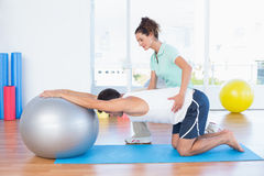 Trainer helping man with exercise ball. Trainer helping men with exercise ball in fitness studio Royalty Free Stock Image