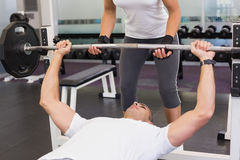Trainer helping man with lifting barbell in gym. Personal female trainer helping young men with lifting barbell in the gym Royalty Free Stock Image