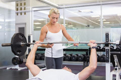 Trainer helping man with lifting barbell in gym. Personal female trainer helping young men with lifting barbell in the gym Royalty Free Stock Photo