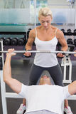 Trainer helping man with lifting barbell in gym. Personal female trainer helping young men with lifting barbell in the gym Royalty Free Stock Images