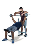 Trainer helping muscular man to lift the barbell Stock Photo