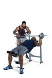 Trainer helping muscular man to lift the barbell Stock Images