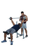 Trainer helping muscular man to lift the barbell Stock Photography