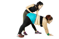 Trainer helping obese woman bending. Female trainer helping obese women bending while wearing sportswear, isolated on white background Stock Images