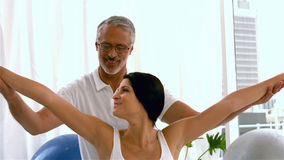 Trainer helping pregnant woman. In studio stock footage