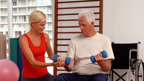 Trainer helping senior citizen work out stock footage
