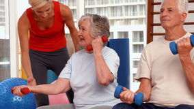 Trainer helping senior citizens work out stock video