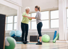 Trainer helping senior woman on bosu balance training platform Stock Images