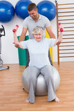 Trainer helping senior woman lift dumbbells on exercise ball. Trainer helping senior women lift dumbbells on exercise ball in fitness studio Stock Image