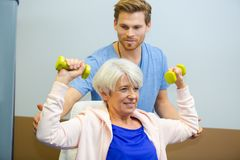 Trainer helping senior woman lift dumbbells in fitness studio. Trainer helping senior women lift dumbbells in fitness studio male Royalty Free Stock Photos