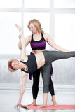 Trainer helping student to do Ardha Chandrasana Pose Stock Images