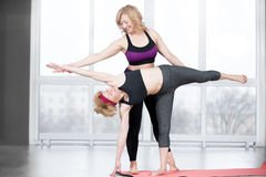 Trainer helping student to do Half Moon Pose Stock Photo
